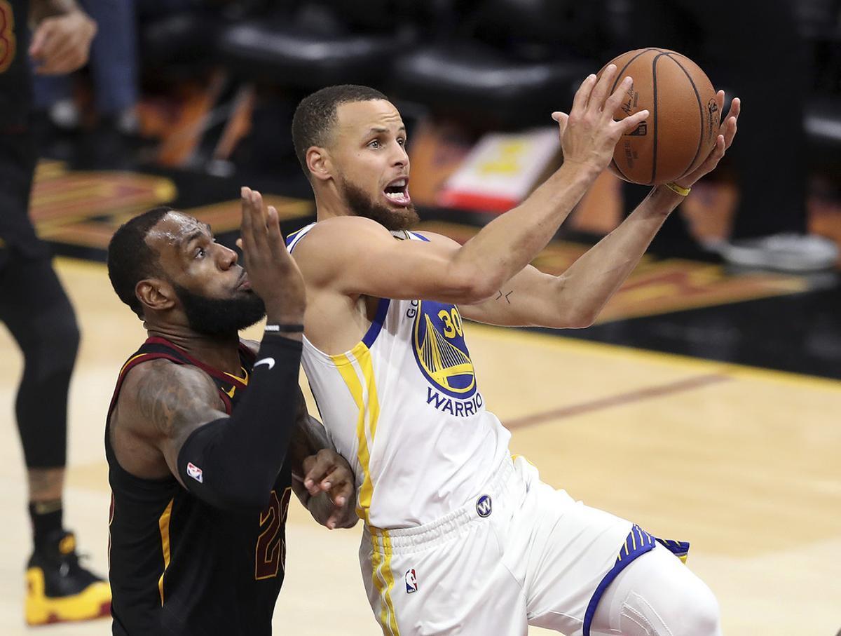 Curry defiende un balón ante la presión de James.