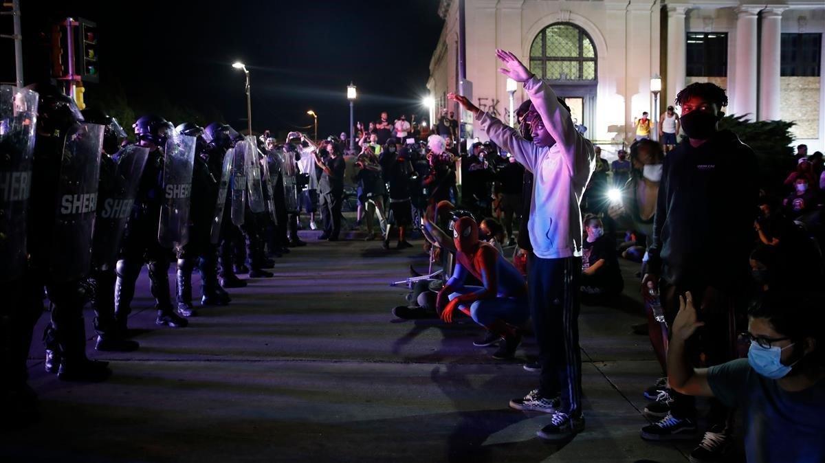 Manifestantes se encaran con la policía durante las protestas contra la violencia racial, la pasada madrugada en Kenosha.