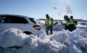 Guardias Civiles quitan nieve en coches que quedaron atrapados durante la nevada en la M-40.