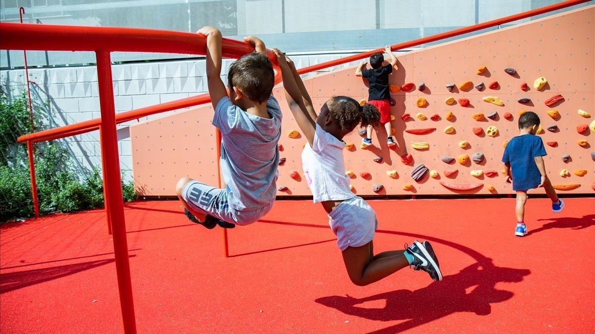 Un grupo de niños juega en una plaza situada frente a la Escola La Pau.