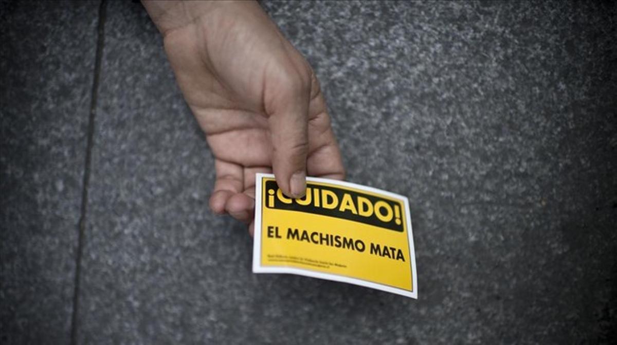 Una mujer sostiene un cartel de advertencia contra la violencia machista, en Buenos Aires