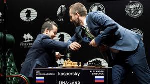 El ruso Ian Nepomniachtchi, a la izquierda,saluda con un toque de codos a su compatriota Alexander Grischuk antes de su partida en el Torneo de Candidatos, en el Hotel Hyatt Regency de Ekaterimburgo.