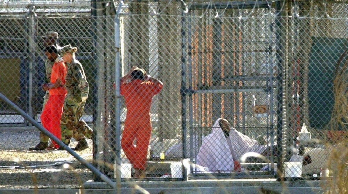 Un recluso de Guantánamo, escoltado por dos guardias en el penal, junto a otros dos presos en sus celdas.