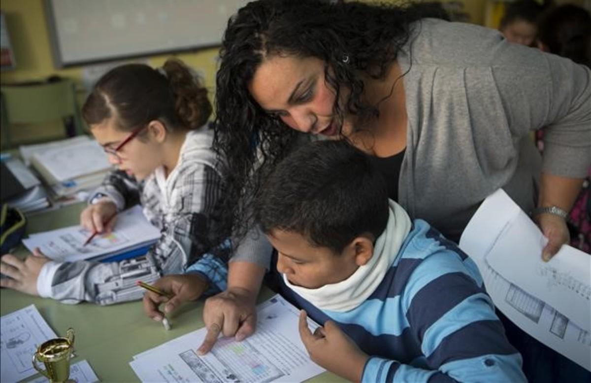 Una madre ayuda a un alumno de primaria en la comunidad de aprendizaje del colegio Joaquim Ruyra de L'Hospitalet de Llobregat.