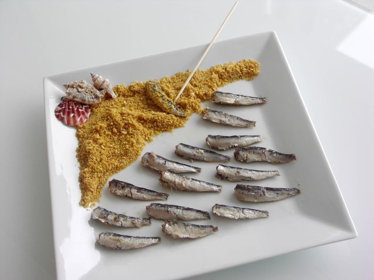 Playa de falsa arena con sardinillas en aceite de oliva.