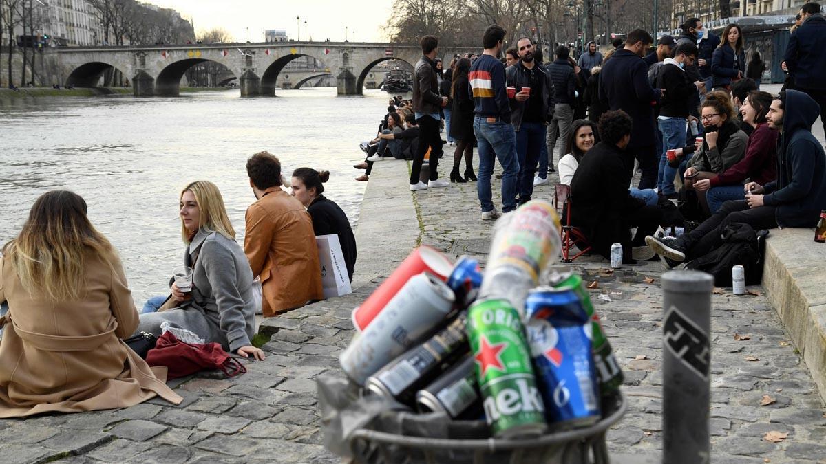 Grupos de jóvenes con bebidas en la rivera del Sena.