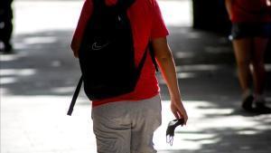 Un hombre pasea con la mascarilla en la mano por las calles de Lleida.