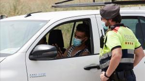 Un mosso detiene a un vehículo en el marco de los controles de movilidad habilitados en la entrada de Soses y otros municipios de Lleida por el rebrote del coronavirus.