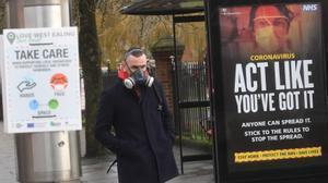 Un hombre, ataviado con una máscara antigás, pasa al lado de un cartel gubernamental para prevenir el contagio de coronavirus, este martes.