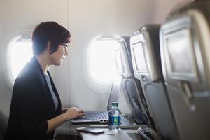 Una usuaria navega por internet a través de wifi en un avión con su portátil.