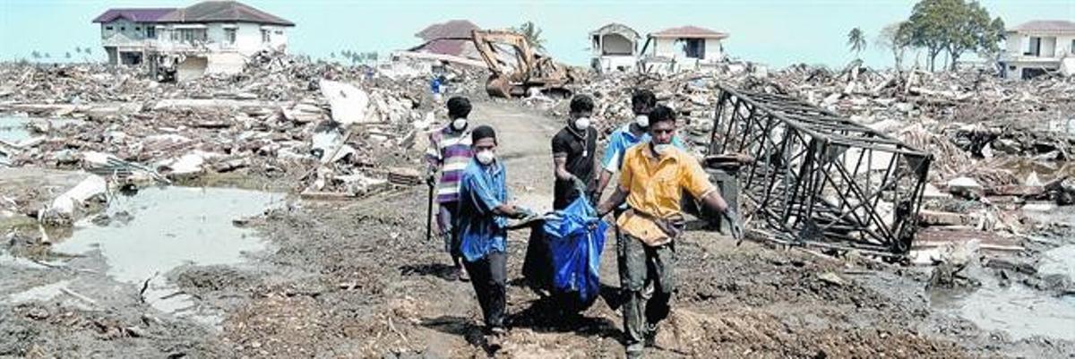 Voluntarios trasladan cadáveres de Ule Lhee, en Banda Aceh, en enero del 2005.