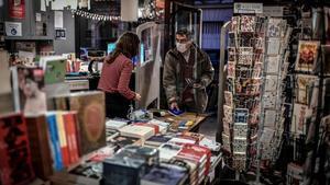 Un hombre recoge un libro encargado previamente en una librería de París, el pasado sábado.