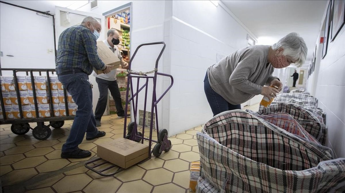 Un pequeño grupo de voluntarios preparara bolsas de alimentos recogidos por, en y para el barrio.