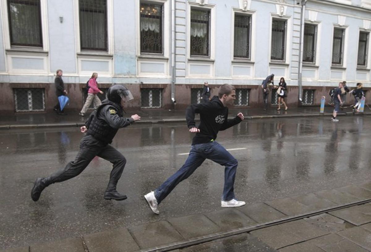 Un policía antidisturbios persigue a un joven que participaba en una manifestación contra el nombramiento de Vladimir Putin en Moscú.
