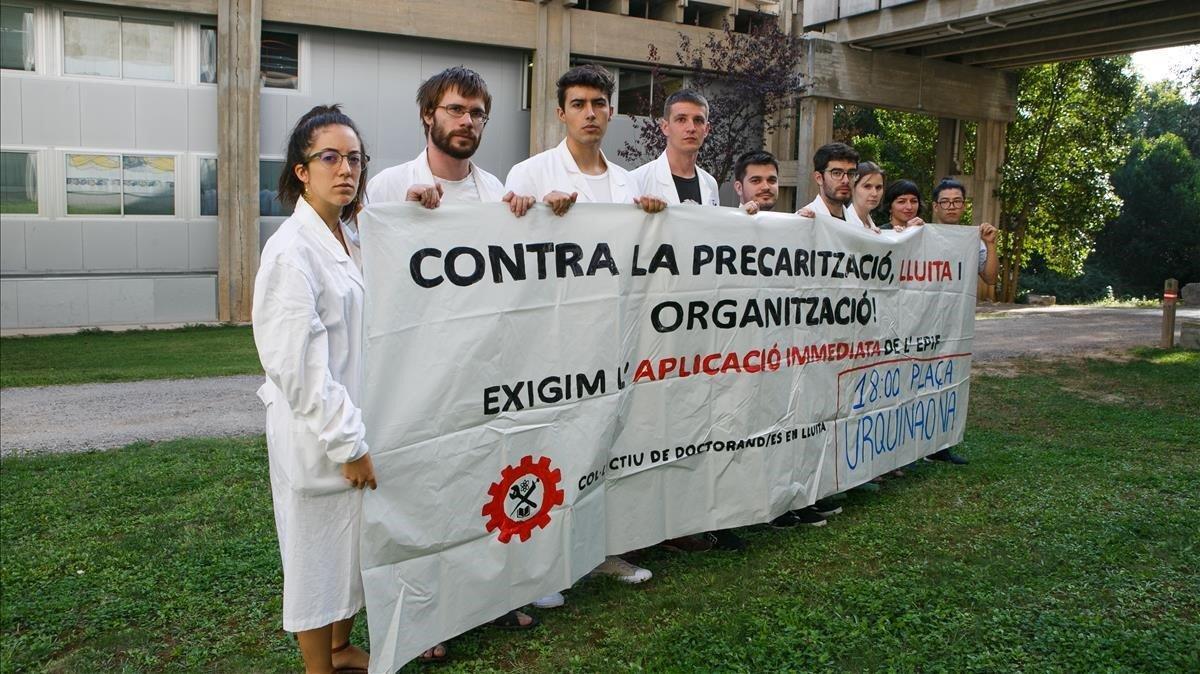 Un grupo de doctorandos sostienen una pancarta que llama a manifestarse por sus derechos, el pasado mes de septiembre.