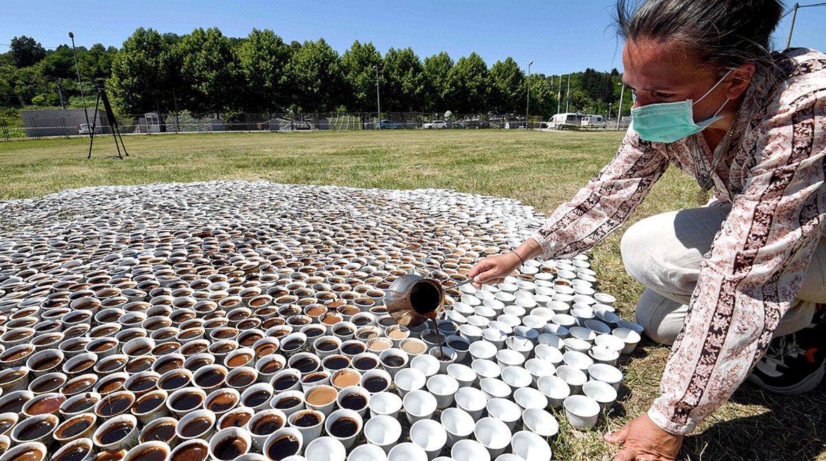 La artista bosnia Aida Šehovićllena las tazas de café de lainstalación '¿Por qué no estás aquí?', cerca del cementerio conmemorativo de la matanza de Srebrenica, en Potocari, el 10 de julio.
