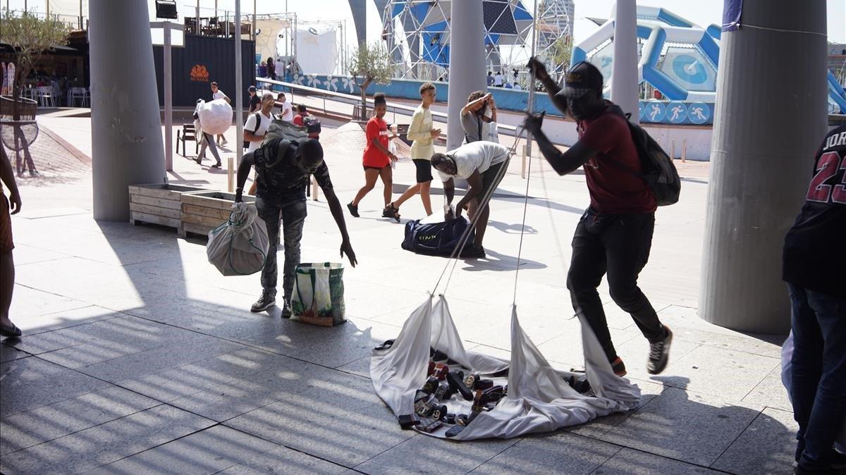 Unos manteros recogen sin poder instalarse en la zona del puerto.