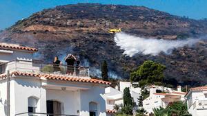 Los bomberos trabajan en la extinción del fuego de Llançà. En la foto, un hidroavión lanza agua cerca de una zona residencial.