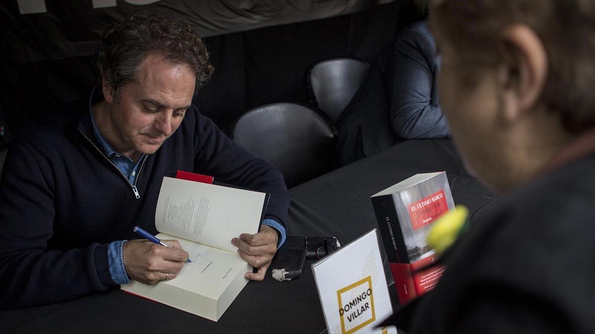 Domingo Villar firma ejemplares en un puesto de la plaza de Catalunya.
