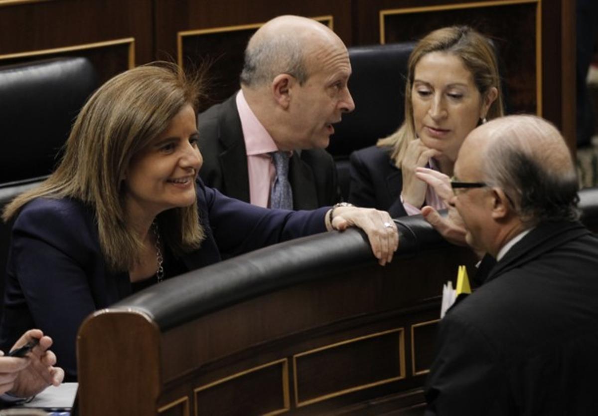 La ministra de Empleo, Fátima Báñez, habla con el titular de Hacienda, Cristóbal Montoro, este jueves, en el Congreso.