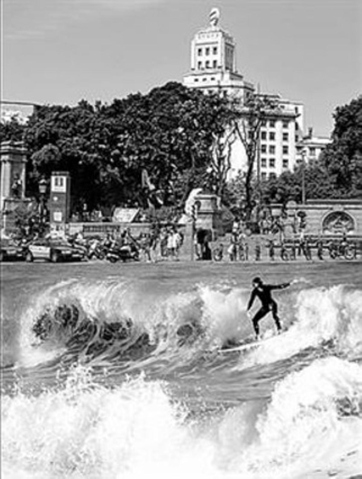 Un surfista de la playa de Sant Sebastià en la plaza de Catalunya.
