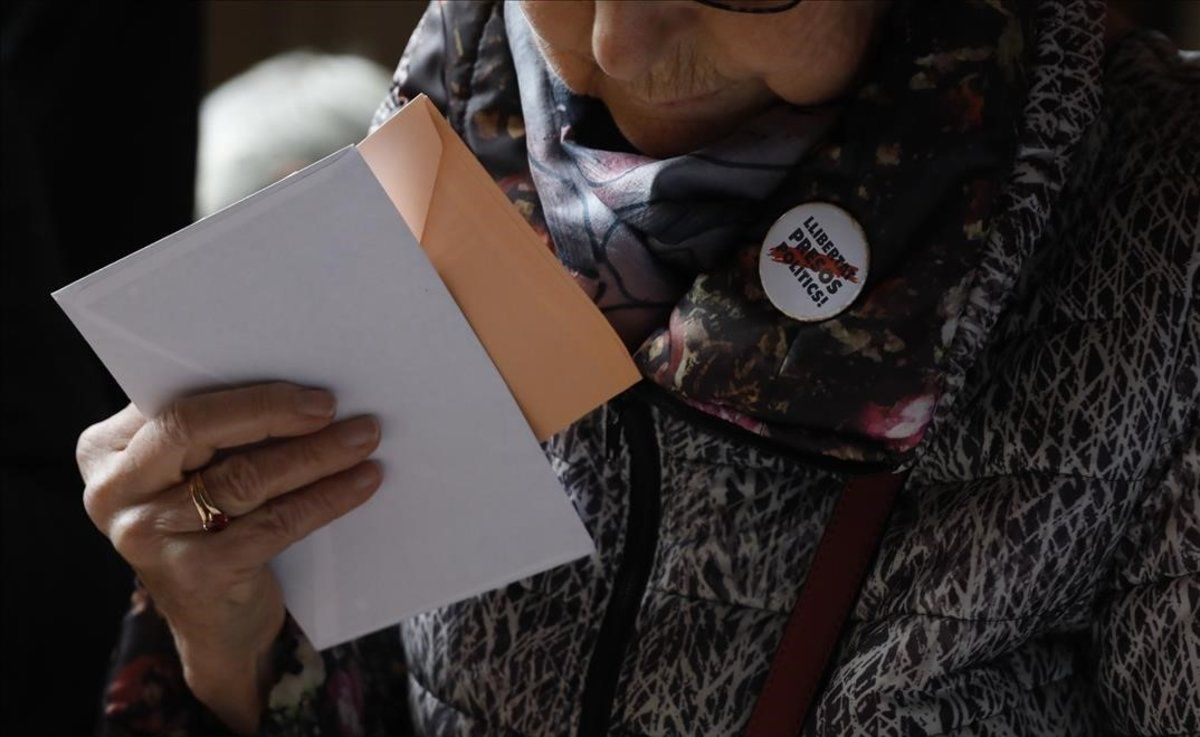 Una mujer escoge las papeletas en el colegio electoral de la Universitat de Barcelona.