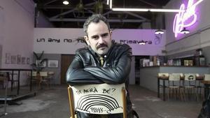 Pau Roca, sentado en una silla con 'mensaje' de La Muriel, un vivero cultural del barrio de Gràcia.