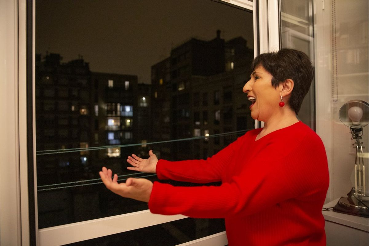 La soprano Begoña Alberdi canta desde el balcón de su casa.