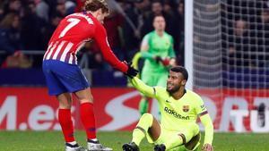 Griezmann ayuda a Rafinha a levantarse en la segunda parte del Atlético-Barça en el Metropolitano.