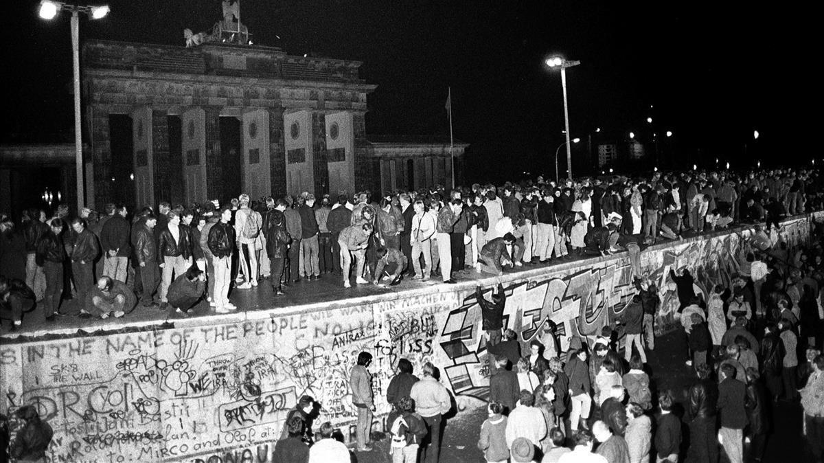 Ciudadanos de Berlín Este y Berlín Oeste celebran sobre el muro el fin de la división de la ciudad, el 9 de noviembre de 1989.
