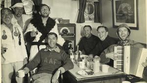 Oficiales y marineros del 'HMS Wyatt Earp' cantan en la cámara del capitán, en febrero de 1948.