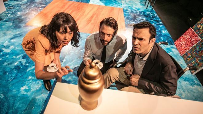 Los tres personajes frente a la urna del padre difunto.