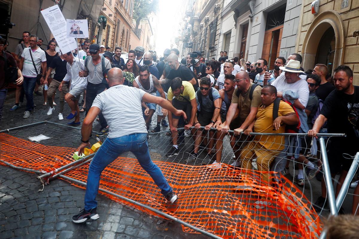 Un grupo de manifestantes contra el pasaporte covid aparta las vallas colocadas por la policía para prevenir su paso en Roma.