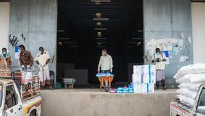 Unos trabajadores humanitarios llevan bolsas de comida a un camión que las distribuirá, en Abyan (Yemen).