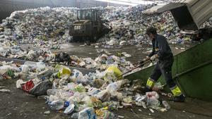 Un operario amontona residuos en la planta de reciclaje de Gavà y Viladecans
