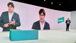 Torra escucha la intervención por videoconferencia de Puigdemont, en el acto inaugural del congreso fundacional del nuevo Junts per Catalunya el pasado 25 de julio.