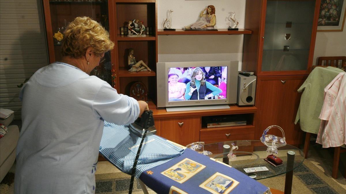 Una mujer plancha en su casa.