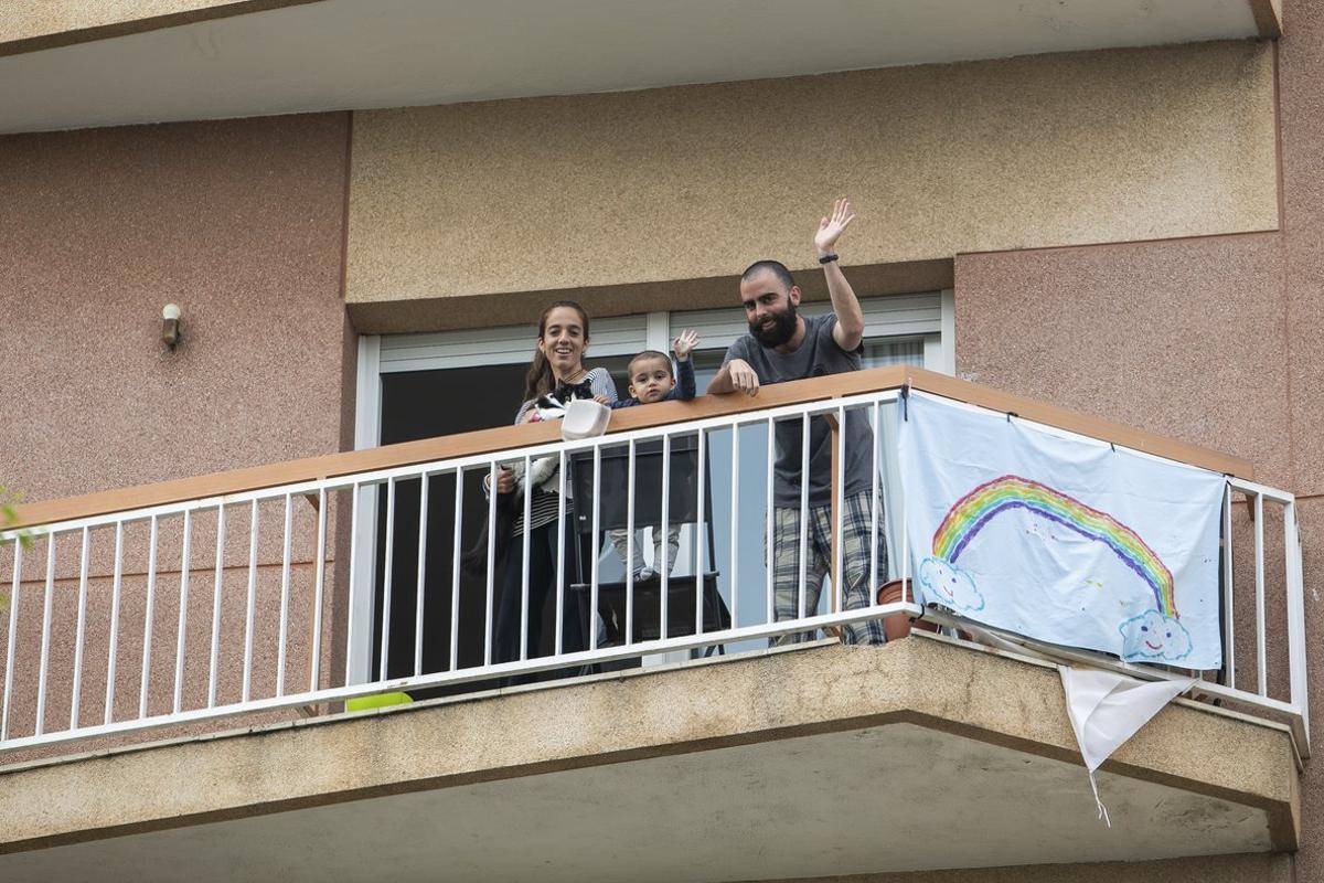 Una familia saluda desde su balcón durante el confinamiento por la crisis del coronavirus.