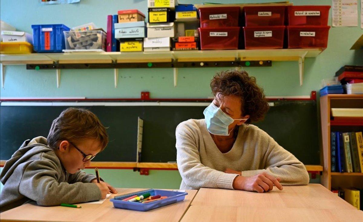 Un profesor con mascarilla habla con un alumno en la escuela Champ l'Eveque en Bruz, Francia.