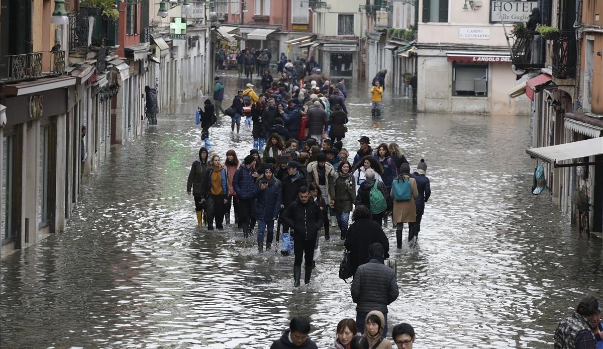 Un grupo de personas recorren una calle anegada en Venecia.
