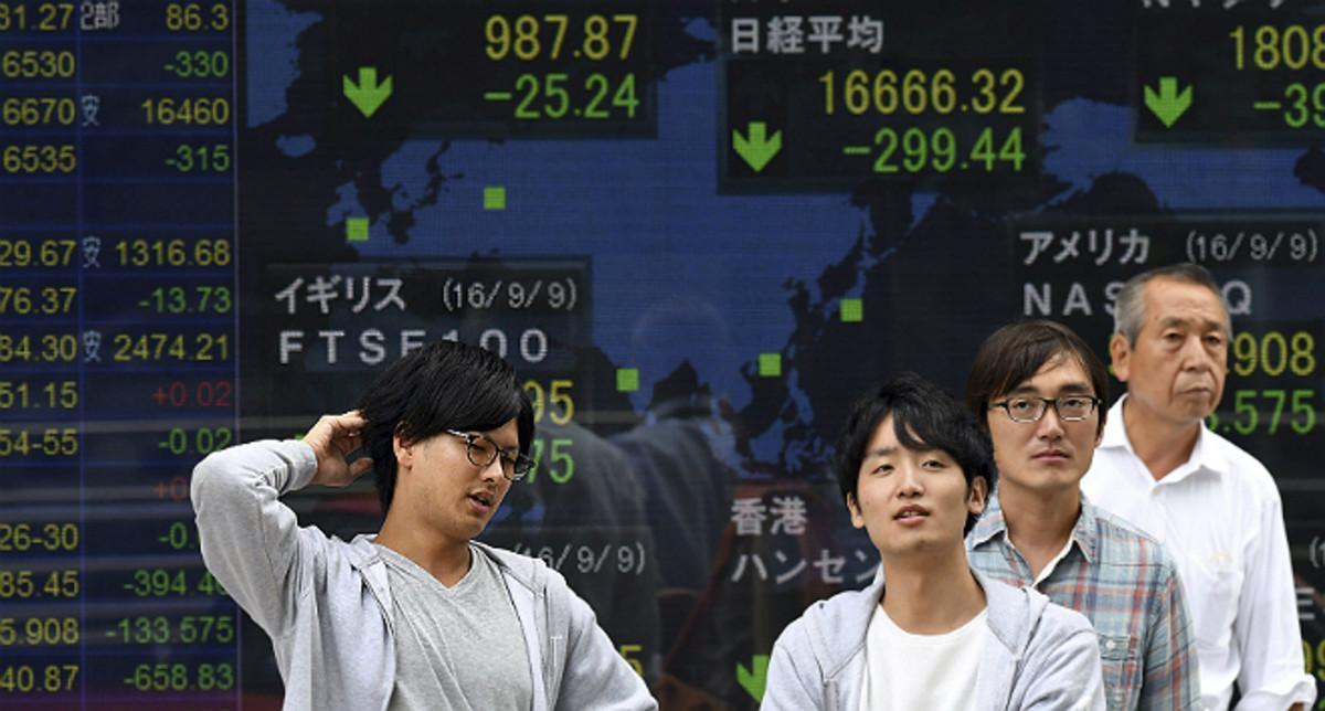Japoneses en Tokio ante un monitor con la evolución de la bolsa.