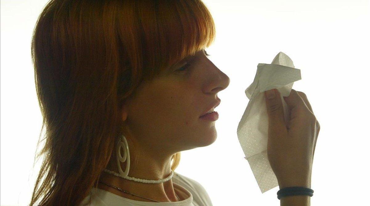 Una mujer estornuda por alergia.