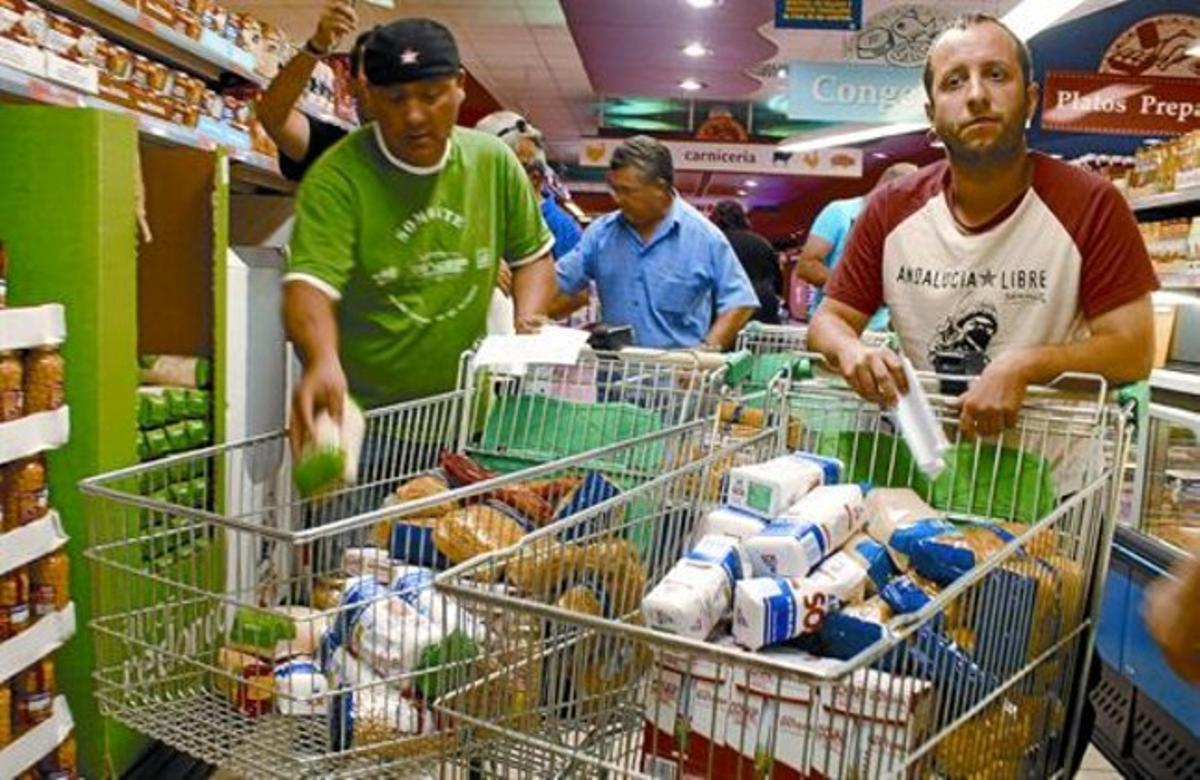 Varios sindicalistas se llevan comida del supermercado de Écija, el martes.