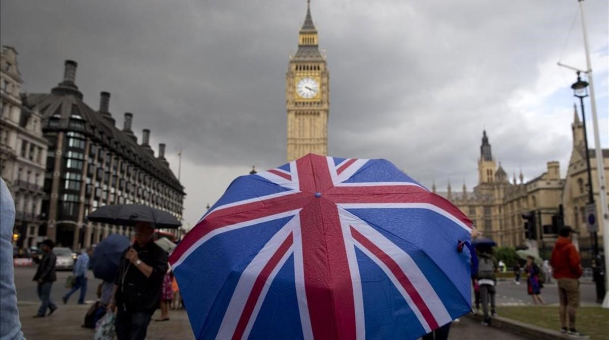 Un transeúnte se refugia de la lluvia en un paraguas con la bandera británica, cerca del Big Ben.