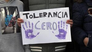 Un manifestante sostiene una pancarta que exige tolerancia cero.