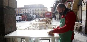 Un camarero prepara la terraza de un pequeño bar.
