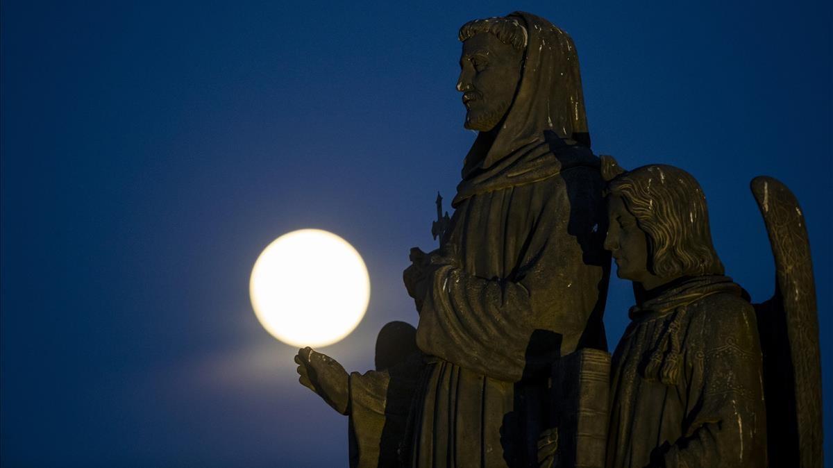 La superluna rosa, tras una de las estatuas del Puente Carlos de Praga, en la República Checa, este lunes.