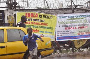 Transeúntes pasan frente a un cartel que alerta del riesgo del ébola en Monrovia, este domingo.