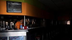 Un empleado de una cafetería de Santa Cruz de Tenerife intenta trabajar a oscuras mientras espera a que se restablezca el suministro eléctrico la isla.