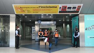 Voluntarios de Protecció Civil, repartiendo mascarillas a las personas usuarias de Ferrocarriles de la Generalitat.
